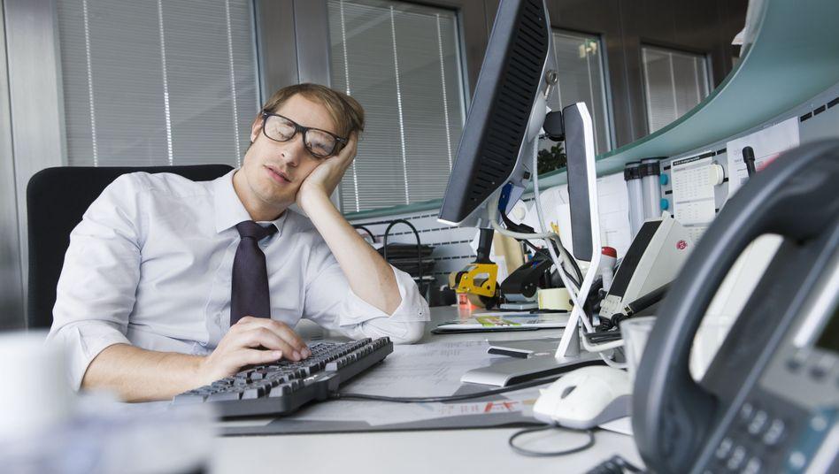 Mittagsschlaf-Möglichkeiten am Arbeitsplatz gibt es noch zu selten. Manche SPIEGEL-Leser machen ihr Nickerchen deshalb direkt am Schreibtisch (Symbolbild)