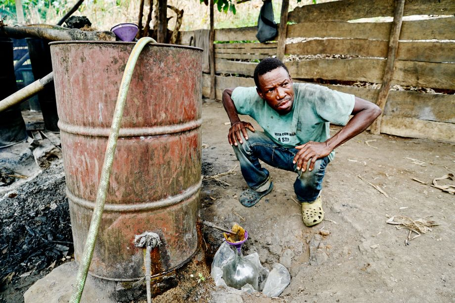 A man squats behind one of the metal barrels in which he distills homemade sugarcane spirits.