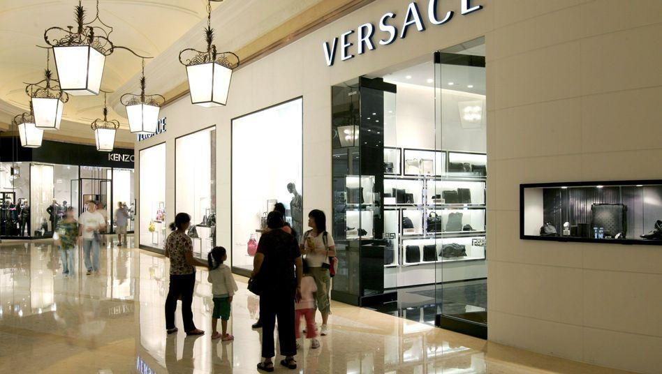 Besucher vor einem Versace-Shop in Macau