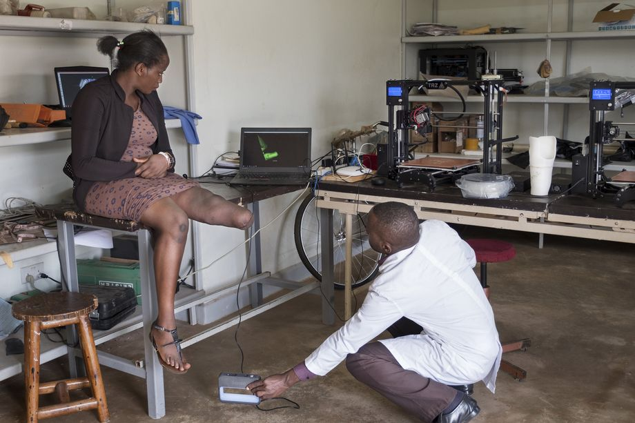 Orthopedic technician Jenan Taremwa scans Gwokyalya's stump, with the data appearing digitally on the screen. The scan only takes a couple of minutes, but printing the socket takes longer than eight hours.