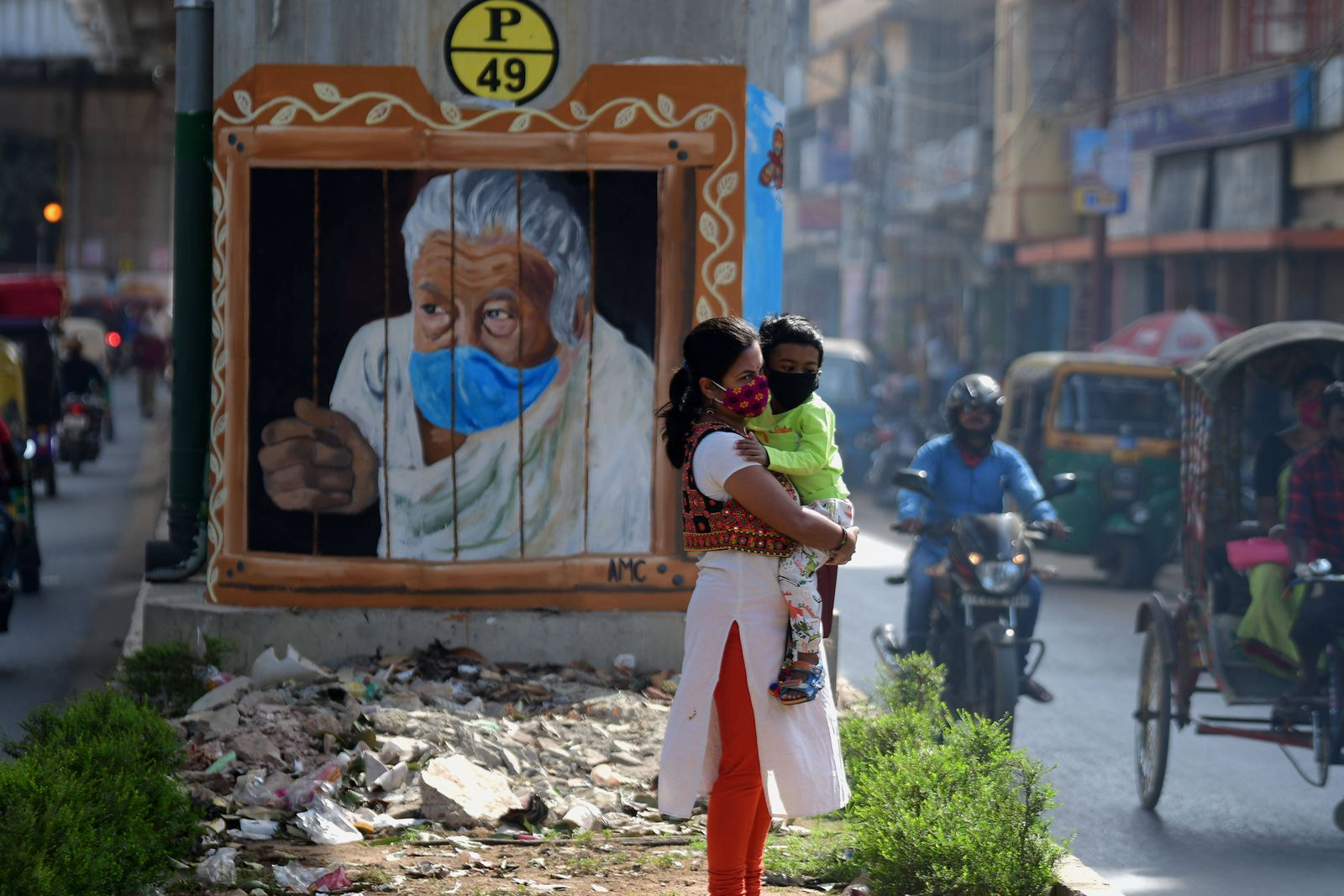 (201125) -- AGARTALA (INDIA), Nov. 25, 2020 -- A woman and a boy wearing face masks are seen in front of a mural in Agar