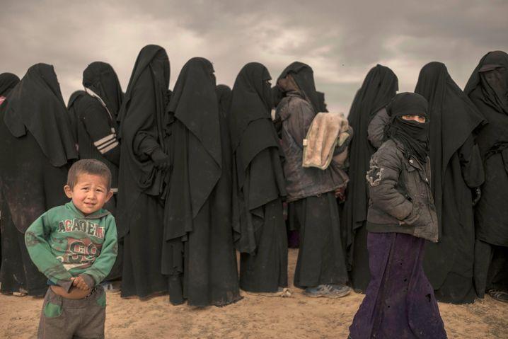 """Frauen und Kinder stehen in einer Schlange an einem Empfangsbereich für Menschen, die aus dem letzten noch von der Terrormiliz """"Islamischer Staat"""" kontrollierten Gebiet im syrischen Baghus ankommen."""