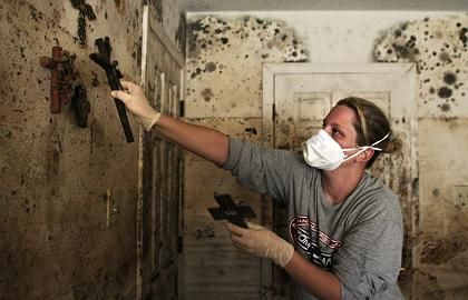 A woman removes crucifixes from the wall of a home in New Orleans destroyed by Katrina.