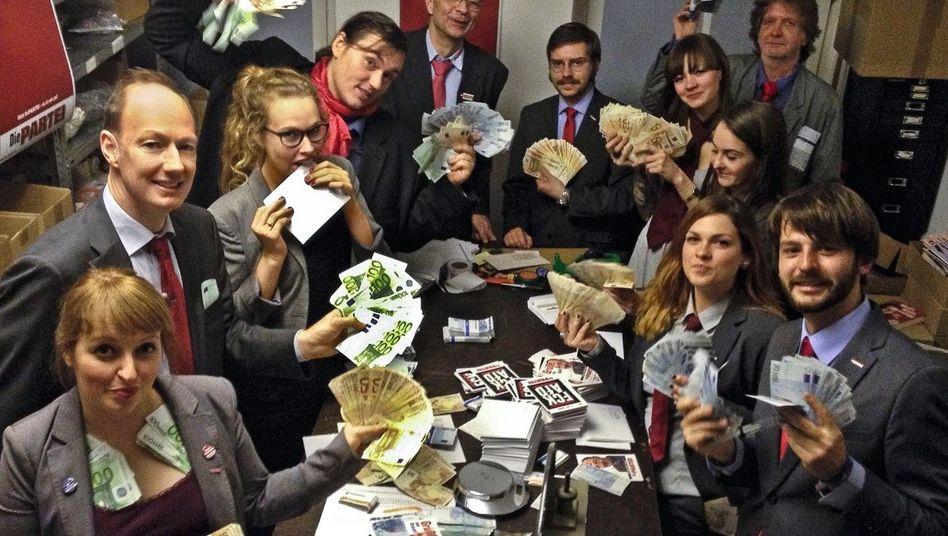 """Mitglieder der Satirepartei """"Die Partei"""" um Martin Sonneborn (l.) beim Geldverkauf 2014"""