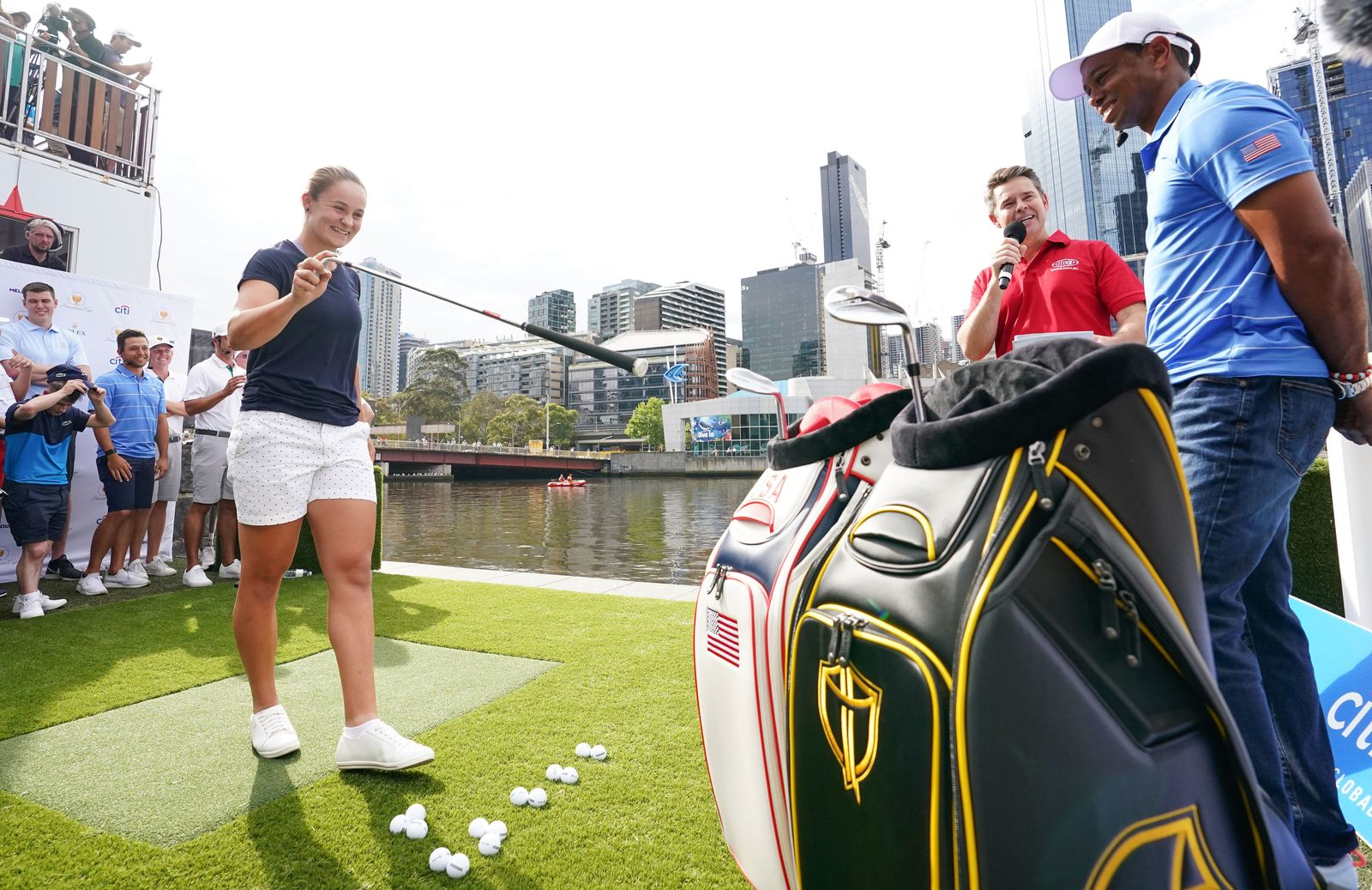 GOLF PRESIDENTS CUP, Ashleigh Barty prepares to play a golf shot as U.S. team Tiger Woods looks on during the Official O