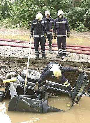 Dresdner Feuerwehrleute untersuchen das Wrack eines Jeeps: Einwohner der Stadt Dresden begannen am Mittwoch mit den Aufräumarbeiten, nachdem der Pegel der Elbe nicht mehr anstieg