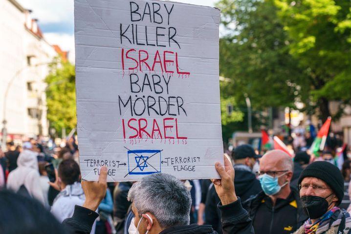 Das Schild, das im Mai bei einer Demonstration in Berlin-Neukölln gezeigt wurde, knüpft an eine jahrhundertealte antisemitische Lüge an. Danach sollen Juden für religiöse Rituale Kinder getötet haben.