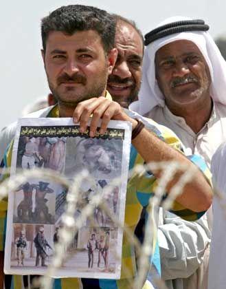 Ein Iraker demonstriert mit einer Zeitung, die die Folterbilder zeigt, vor dem Gefängnis von Abu Ghureib