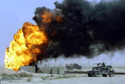 Ein Konvoi von US-Marines passiert auf dem Weg nach Bagdad eine angeblich von irakischen Truppen in Brand gesteckte Ölquelle im al-Ratka-Ölfeld