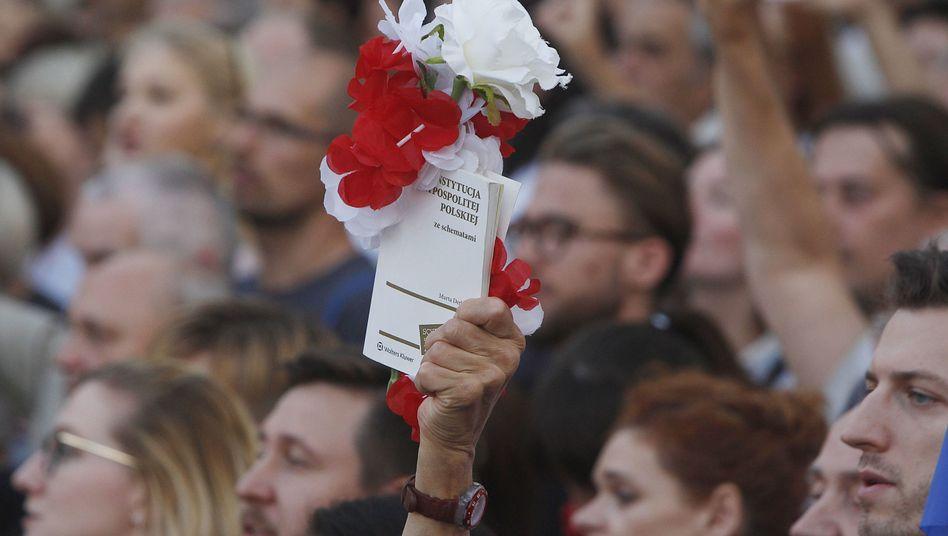 Gegner der umstrittenen Justizreform halten vor dem Sejm in Warschau eine mit polnischen Farben geschmückte Verfassung hoch (Archivbild)