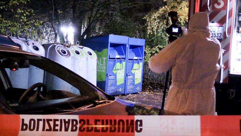 Ein Mitarbeiter der Spurensicherung fotografiert vor Glas- und Kleidercontainern am Rand eines Waldes in Duisburg