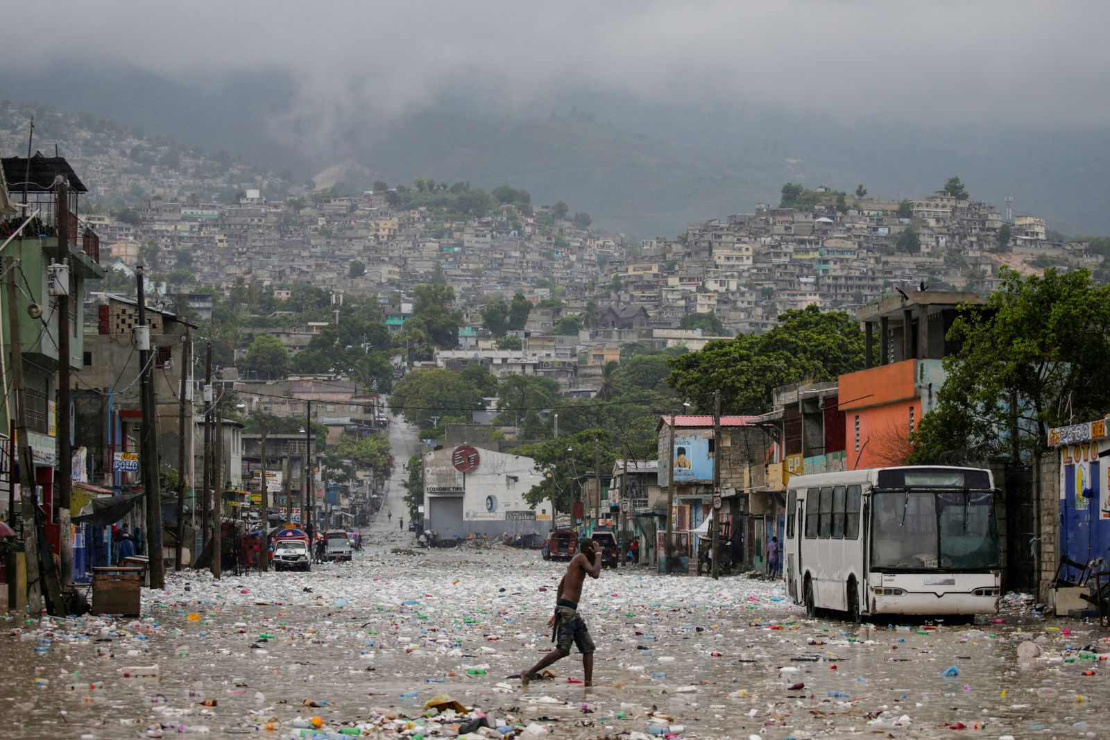 A man walks in a flooded street during the passage of Tropical Storm Laura, in Port-au-Prince