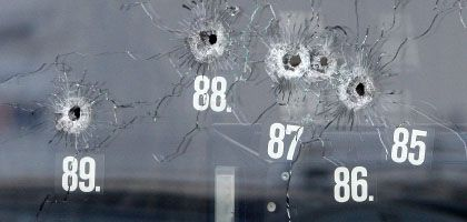 Bullet holes in the window of the car dealership where Tim K. made his last stand on Wednesday.