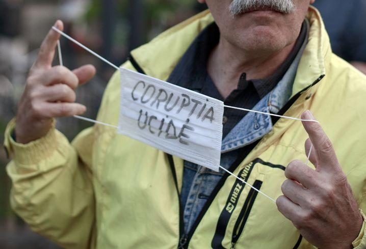 """""""Korruption tötet"""" steht auf dieser Maske eines Protestierers"""