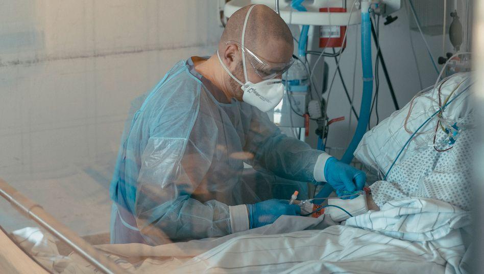 Krankenhausmitarbeiter, Covid-19-Patient auf Intensivstation
