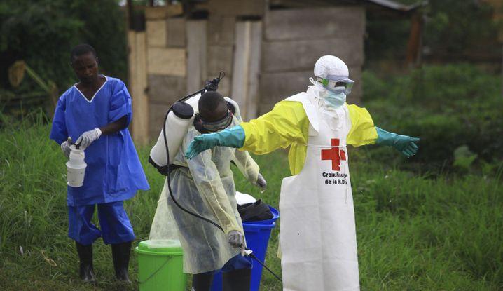 Ein Helfer vom Roten Kreuz wird nach einem Einsatz in einem Ebola-Behandlungszentrum von einem Kollegen mit Desinfektionsmittel eingesprüht.