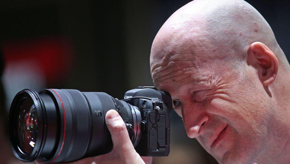 Ein Messebesucher testet eine spiegellose Digitalkamera
