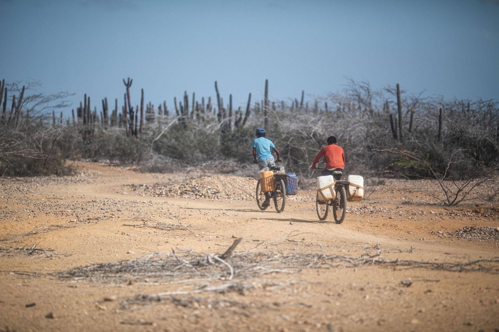 Zwei Jugendliche fahren mit einem Fahrrad mit Wasserkanistern durch die Wueste La Guajira in Kolumbien, aufgenommen bei