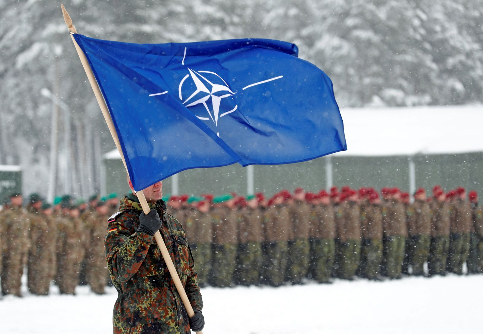 A soldier carries the NATO flag during German Minister of Defence Ursula von der Leyen's visit to German troops deployed as part of NATO enhanced Forward Presence (eFP) battle group in Rukla military base