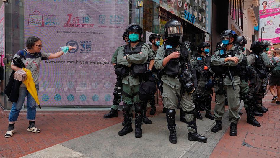 Eine Frau und Polizisten in voller Montur in Hongkong