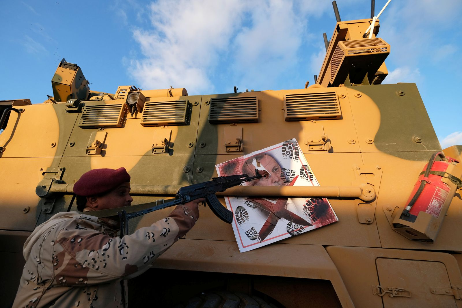 A member of Libyan National Army (LNA) commanded by Khalifa Haftar, points his gun to the image of Turkish President Tayyip Erdogan hanged on a Turkish military armored vehicle, which LNA said they confiscated during Tripoli clashes, in Benghazi