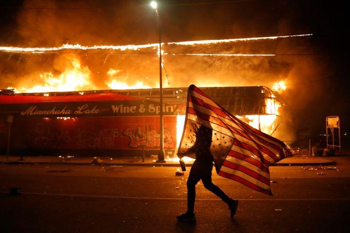 Demonstrant mit US-Flagge vor brennendem Spirituosengeschäft in Minneapolis