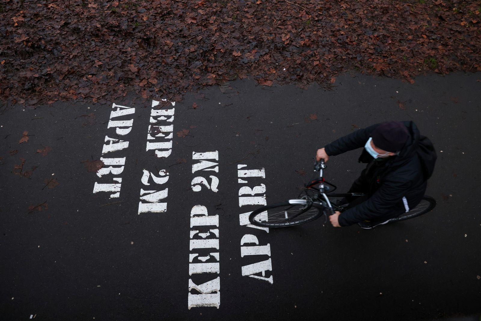 A man wearing a face mask rides a bike near a warning sign on Eel Brook Common