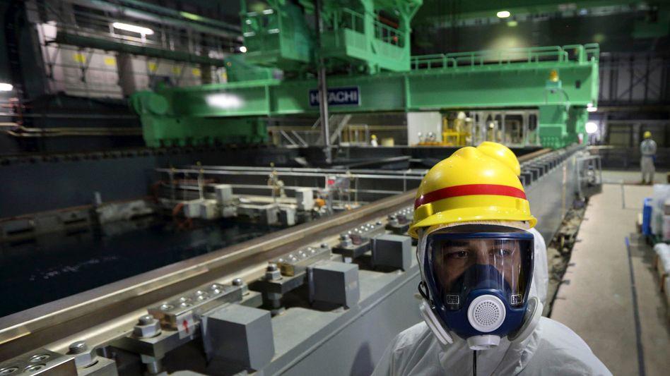 Sicherheitsmitarbeiter am Reaktor 4 des havarierten Atomkraftwerks (7. November 2013): Betreiber Tepco will Teile des AKW zu Forschungszwecken freigeben
