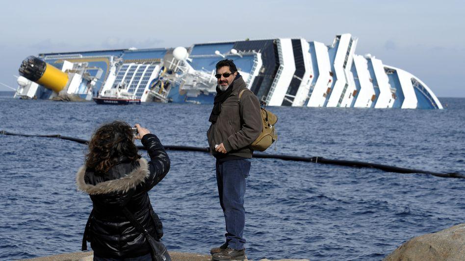 """Attraktion auf Giglio: Schaulustige posieren vor dem Wrack der """"Costa Concordia"""""""