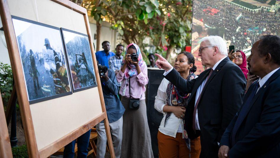 Bundespräsident Steinmeier schaut im Garten der Residenz des deutschen Botschafters Fotos vom Aufstand 2019 im Sudan an