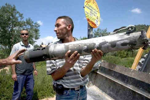 A Israeli man holds a part of a Katyusha rocket at the main road of the northern Israeli town of Safed on July 14.