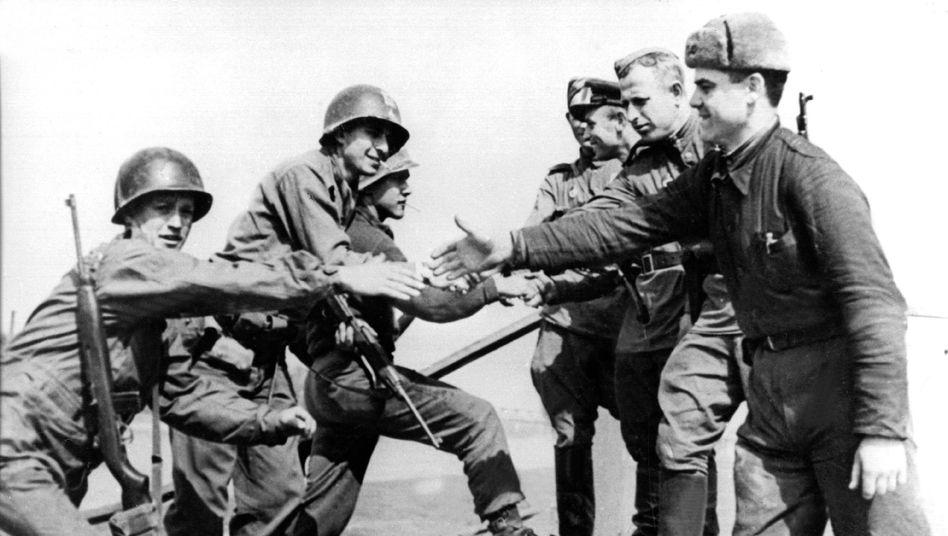 Kurz vor Kriegsende: Amerikanische (l.) und sowjetische Soldaten reichen sich auf den Trümmern einer Elbbrücke bei Torgau die Hände (25. April 1945)