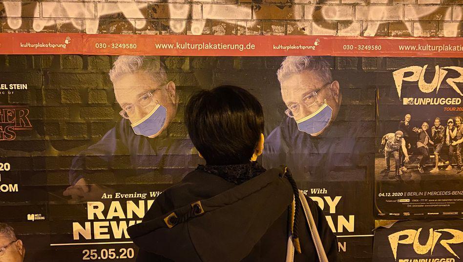Werbeplakat für den Auftritt des Musikers Randy Newman in Berlin beklebt mit Mundschutz
