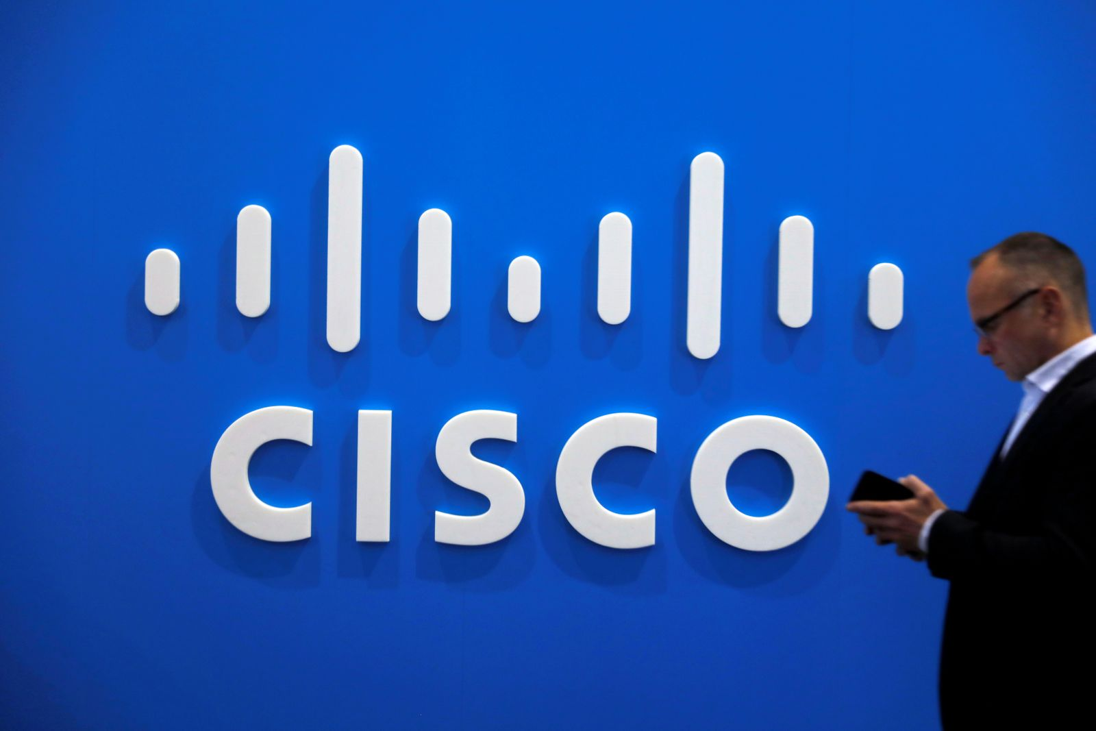 FILE PHOTO: A visitor uses a mobile phone in front of the Cisco booth at the Mobile World Congress in Barcelona
