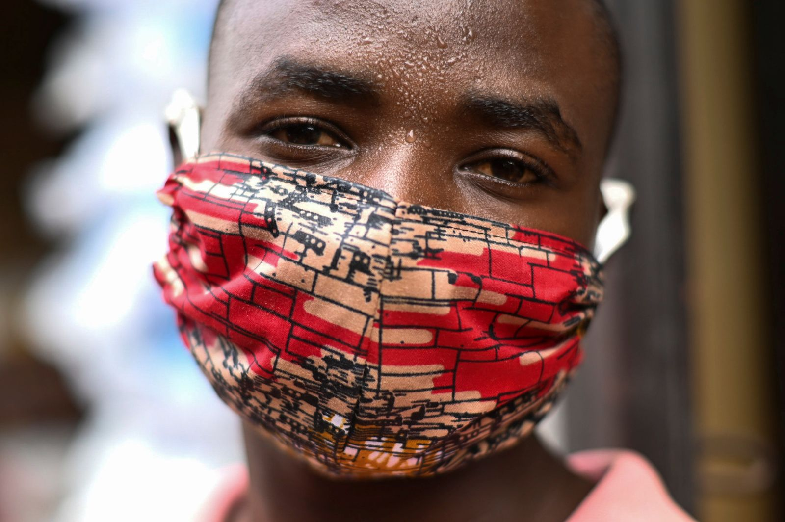 "Pierre Mahiraguha, a vendor at the Kimironko market wears a handmade ""kitenge"" cloth mask as he attempts to protect against the coronavirus disease (COVID-19), in Kigali"