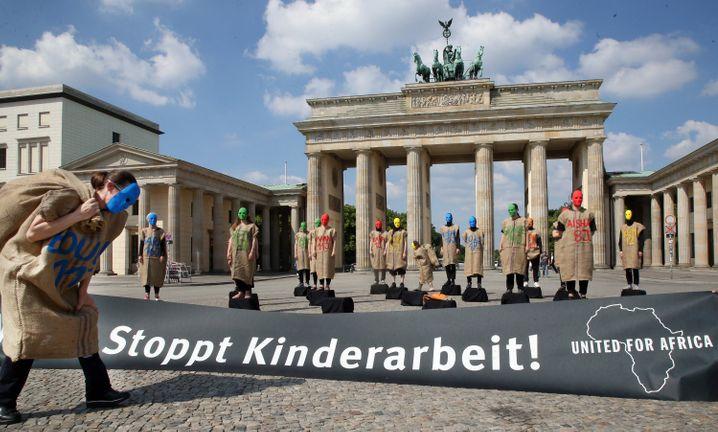 Mitglieder des Bündnisses Gemeinsam für Afrika protestieren vor dem Brandenburger Tor gegen Kinderarbeit