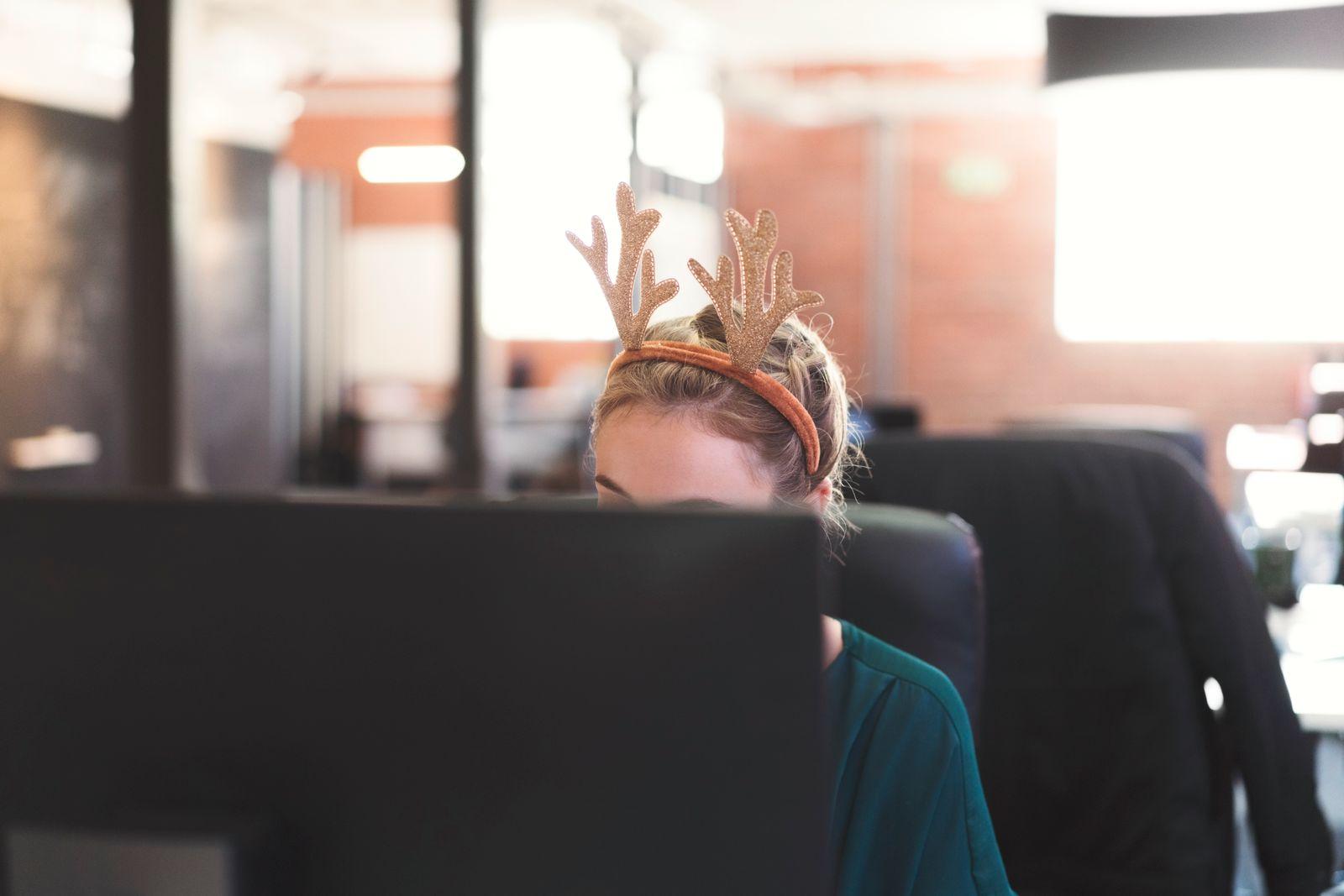 Businesswoman wearing reindeer antlers at office