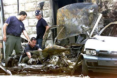 Anschlag in der City: Polizeibeamte untersuchen das Wrack des Autos, in dem am Sonntagmorgen eine Bombe detonierte