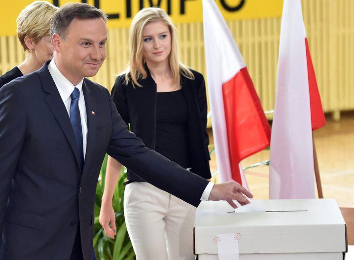 Duda bei der Stimmabgabe mit Ehefrau Agata (verdeckt) und Tochter Kinga: Kein polternder Volkstribun