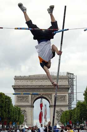 """An athlete jumps near the Arc de Triomphe as the City of Paris promotes its 2012 olympic bid with a parade and sport demonstrations on the Champs Elysees called """"l'Amour des Jeux"""" (The love of the Games)."""