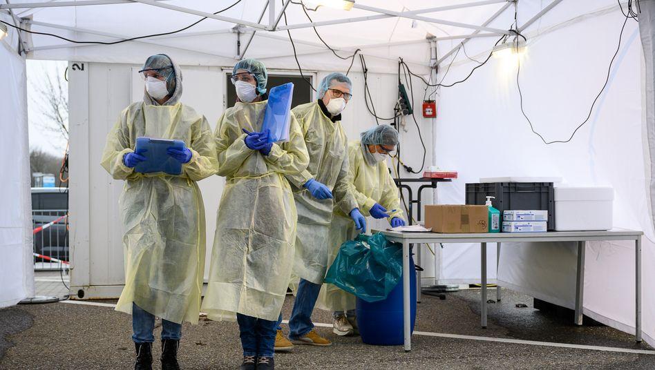 Deutschland testet: Mitarbeiterinnen und Mitarbeiter eines Corona-Abstrich-Zentrums an der Messe Stuttgart