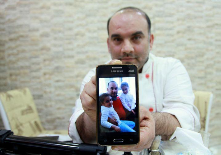 Talal Sourouji zeigt ein Foto von seinen Kindern und sich