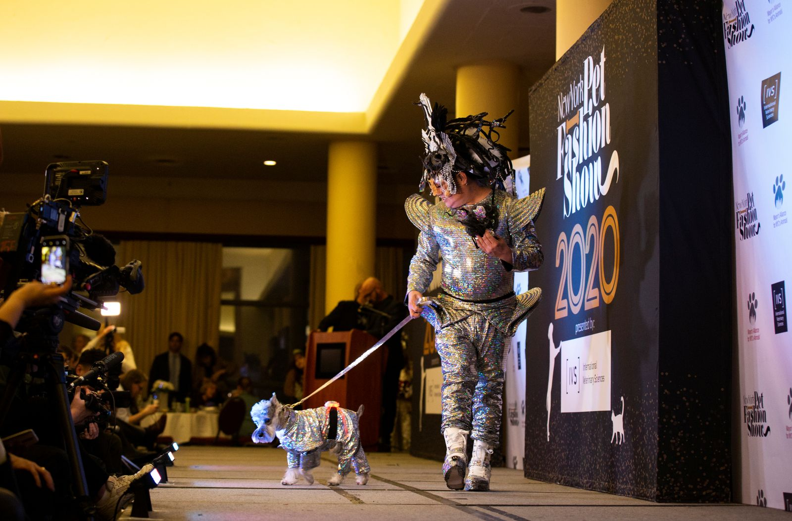 A man walks a dog across the runway stage at the 17th annual New York Pet Fashion Show