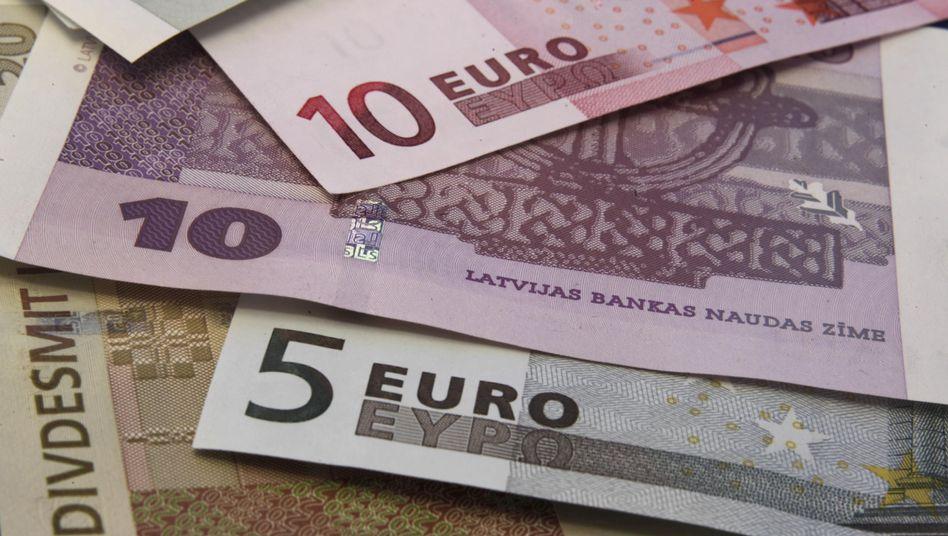 Euro-Scheine und lettische Lats: Staat erfüllt alle Maastricht-Kriterien
