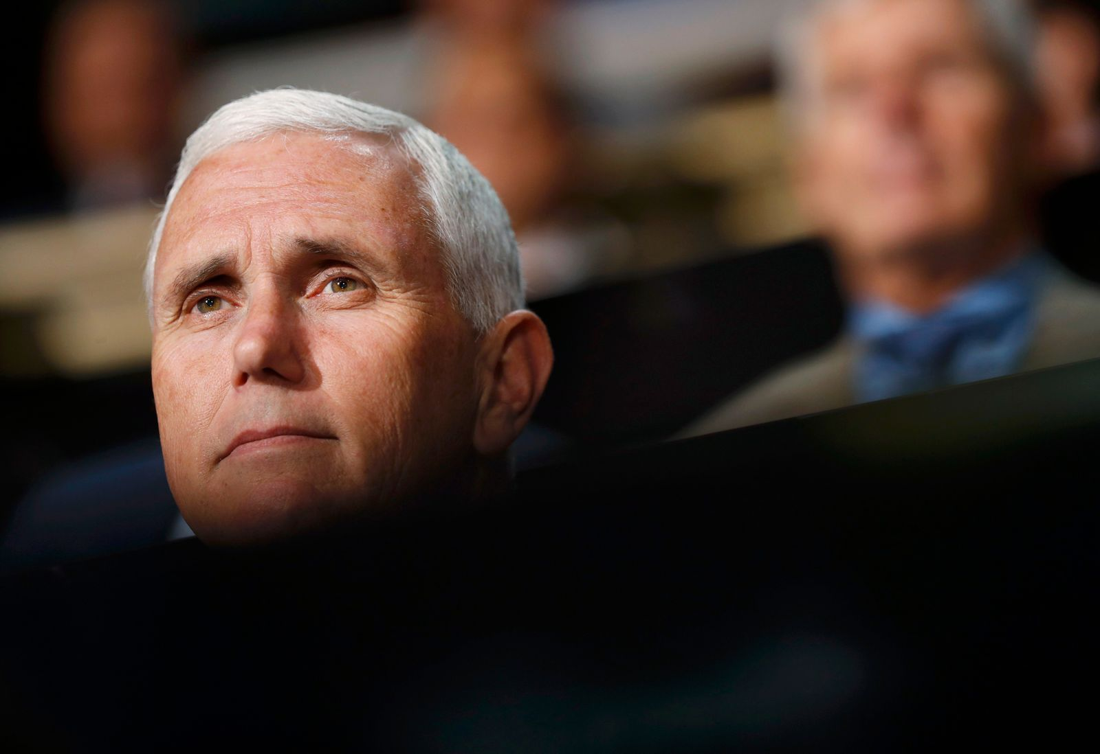 Republican U.S. vice presidential nominee Mike Pence (L) listens to speeches at the Republican National Convention in Cleveland