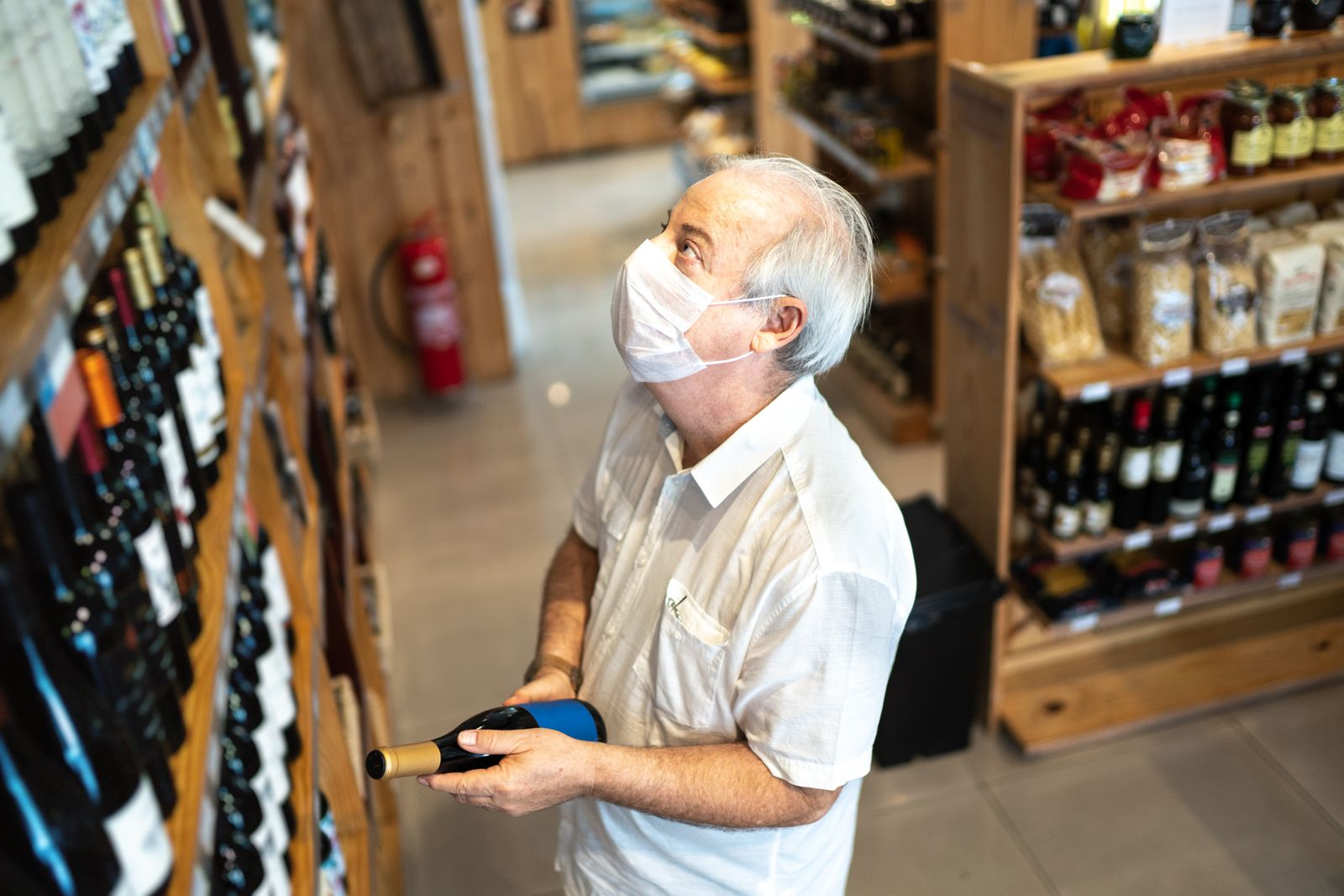 Senior man buying wine with face mask at store