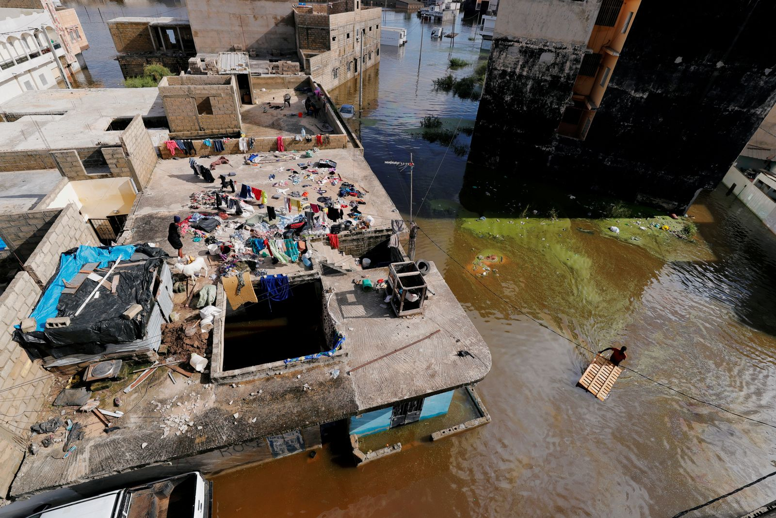 A resident makes his way through a flooded street while a woman hangs clothes to dry on a terrace in Keur Massar,