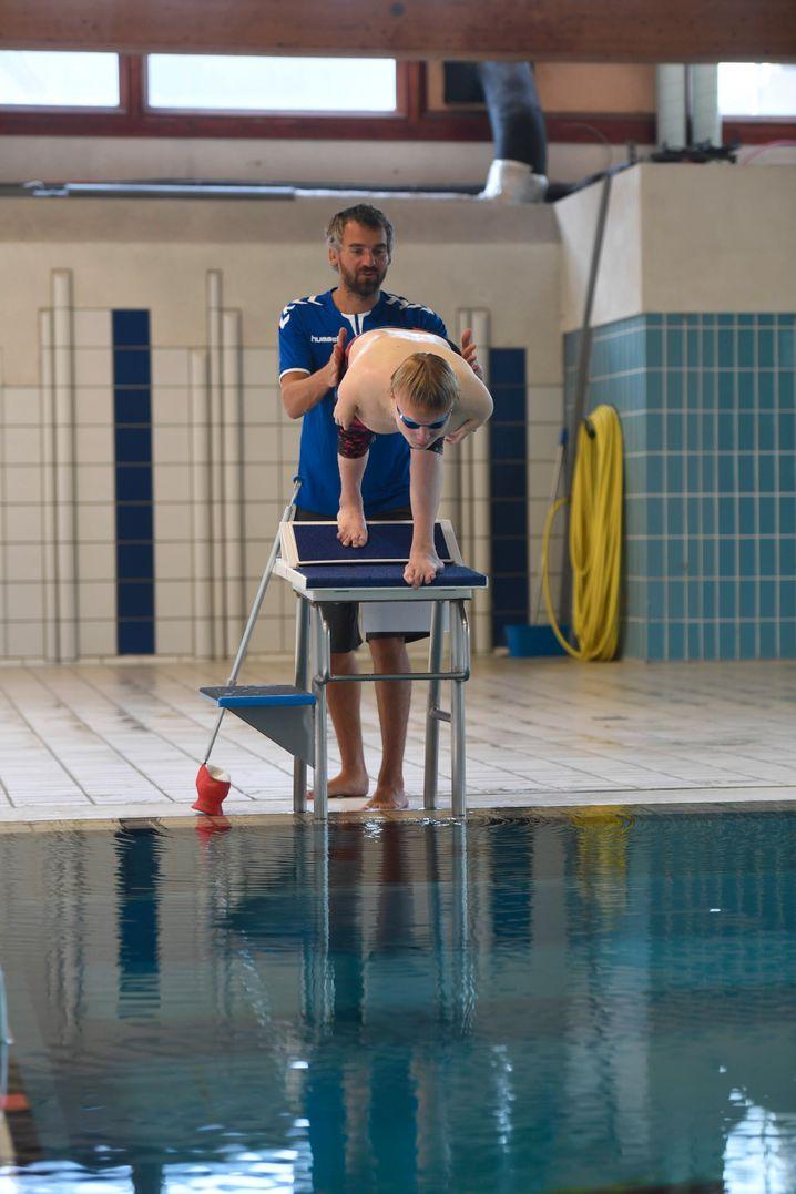 Chris hilft Josia, bevor es ins Wasser geht. Erst beim Abnehmen der Beinprothesen, anschließend am Startblock, damit Josia vor dem Sprung ins Becken nicht das Gleichgewicht verliert.