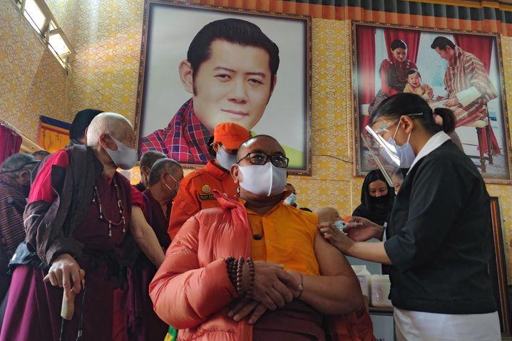 Ein buddhistischer Mönch erhält seine erste Corona-Impfung in Bhutan, im Hintergrund: ein Porträt des Königs. Das Land hat innerhalb einer Woche mehr als 80 Prozent der Erwachsenen geimpft.