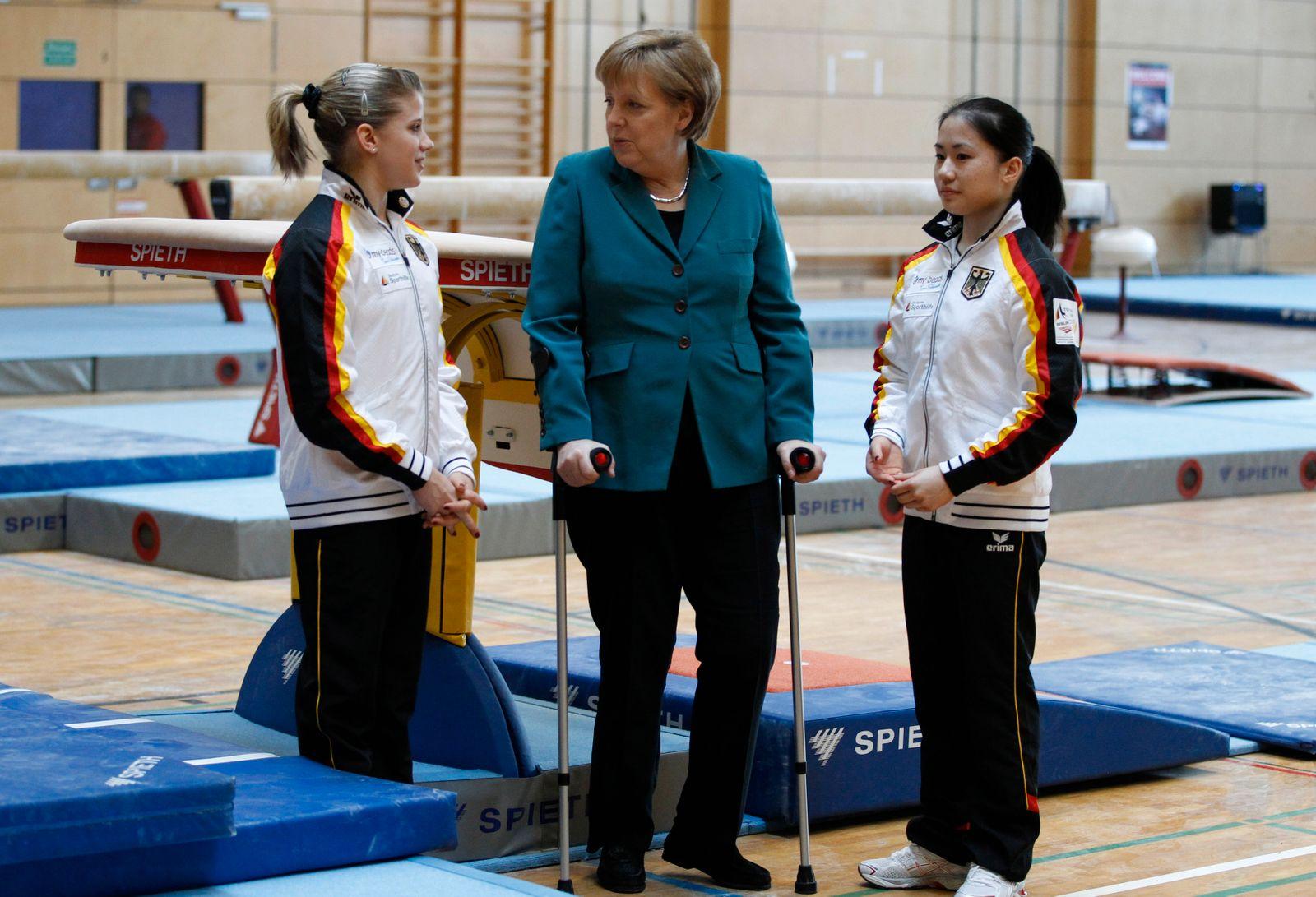 German Chancellor Merkel talks to members of German national team before official opening of Artistic Gymnastics European Championships in Berlin
